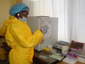 Mitarbeiterin der SOS-Klinik in gelbem Schutzanzug.